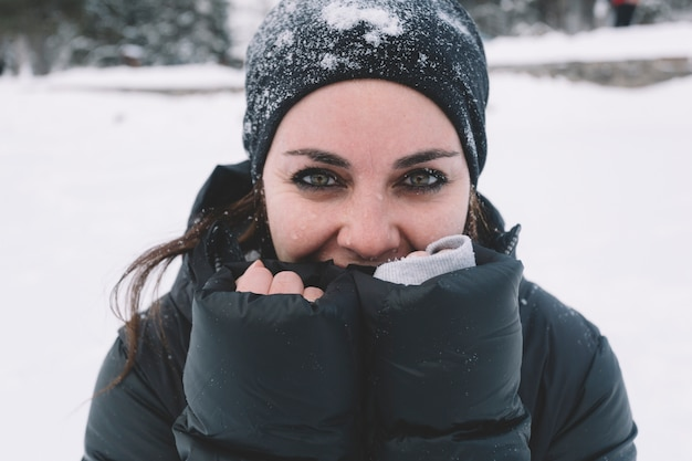 Woman warming hands on snowy background