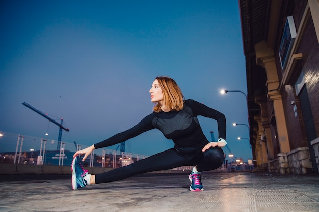 Woman warming up legs on pavement