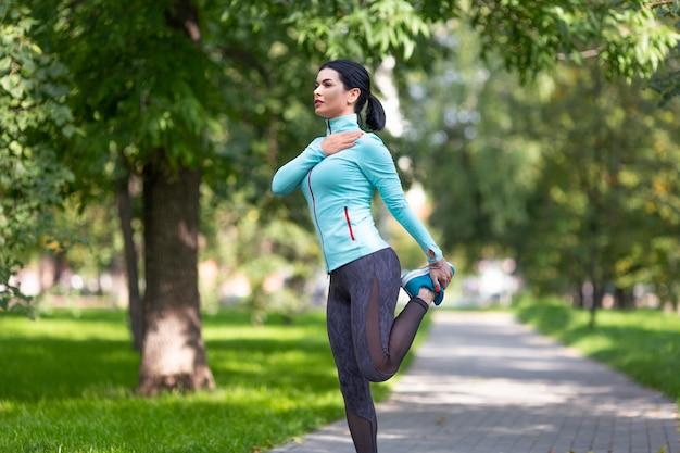 Женщина разогревает мышцы перед бегом на открытом воздухе в летнее время