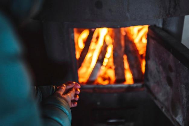 小屋の暖炉の近くでウォーミングアップする女性