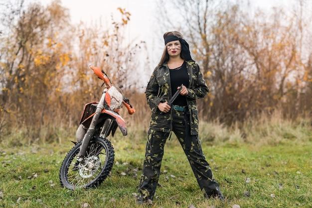 Женщина-воин в камуфляжной форме позирует на открытом воздухе