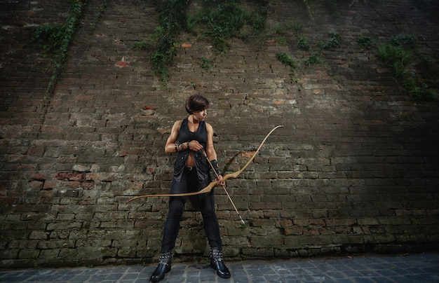 Woman warrior prepare for shooting from bow.
