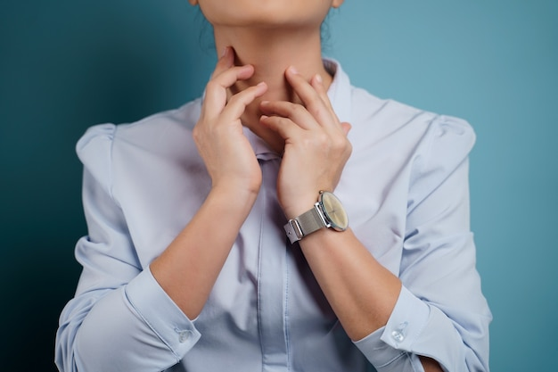Woman was sick with sore throat isolated on blue.