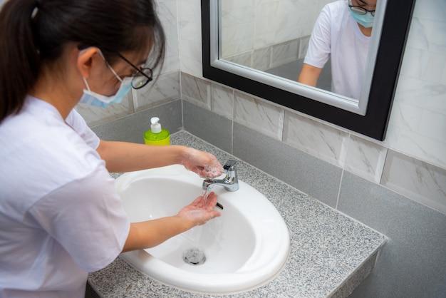 Женщина моет руки с мылом в раковине, дезинфекция, чтобы остановить коронавирус или предотвратить распространение вспышки covid 19, хорошая гигиена защищает и быть в безопасности от вируса короны