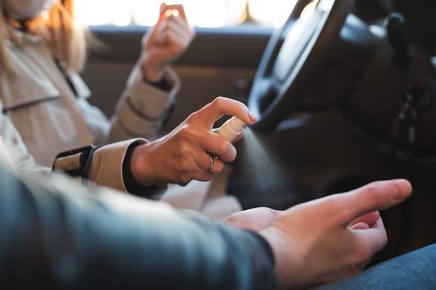 女性はコロナウイルスの感染を防ぐために手指消毒剤で男性の手を洗います