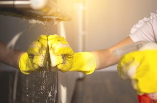 노란색 스폰지와 스프레이 병으로 주방과 전기 오븐을 세척하고 청소하는 여성, 근접 촬영 보기 및 선택적 초점 사진
