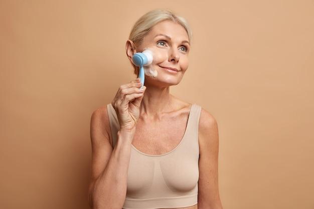 La donna lava il viso con la spazzola e la schiuma detergente si prende cura della pelle della carnagione