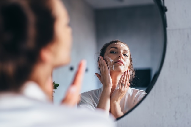 女性は鏡の前で顔を洗い、頬に泡を塗ります。