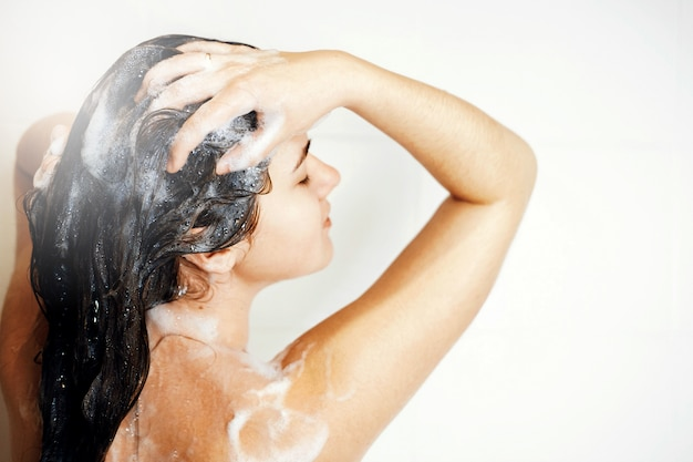 Woman washes her hair in shower, takes a shower, steam coming, foam on hair
