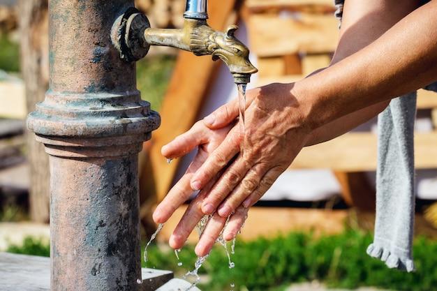 女性は通りの蛇口の下で手を洗います