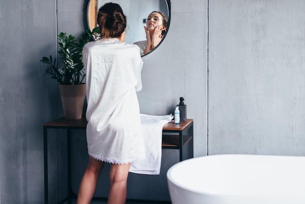 여자는 거울 앞에서 씻고 얼굴에 거품을 바릅니다.
