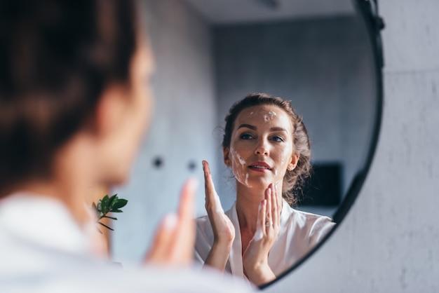 女性は鏡の前で洗って顔に泡を当てる