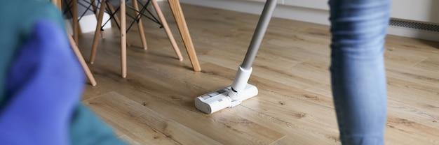 女性はノズル付きモップで軽い床を洗う