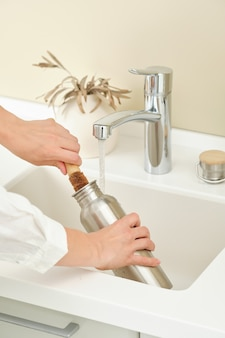 Woman washes a metal reusable bottle with a coconut brush washing dishes without chemicals woman