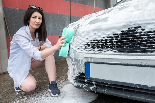 女性がスポンジと泡で車を洗う