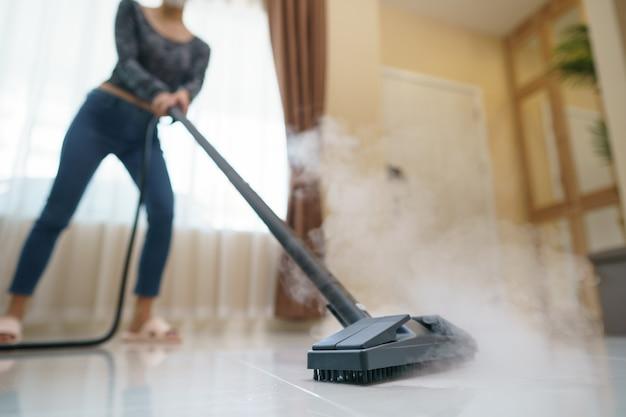 女性はスチームモップで床を洗います。