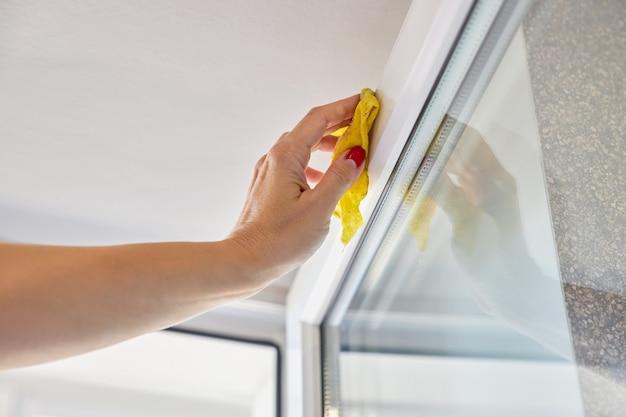 女性は黄色い布で開いているウィンドウのフレームを洗う