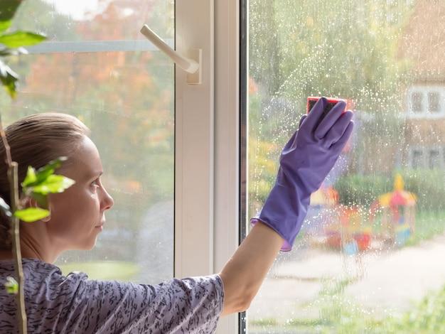 여자는 스폰지로 창을 씻어. 집 청소. 겨울에는 더러운 창문 유리 세제를 씻으십시오.