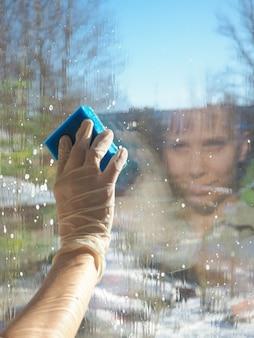 女性がスポンジで窓を洗う