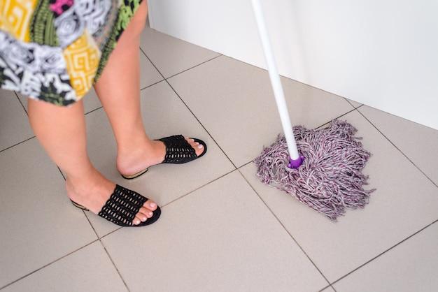 女性は濡れたモップ、ハウスキーピングのコンセプト、クローズアップで床のタイルを洗う