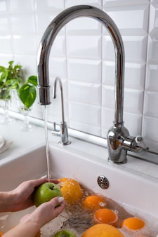 Woman washing apple under faucet in the sink kitchen, soaking fruits in soapy water thoroughly washes after store