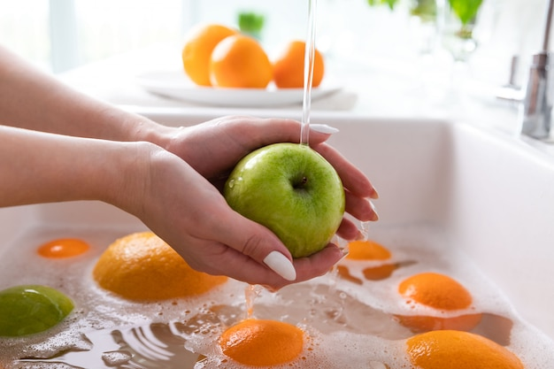 Woman washing apple under faucet in the sink kitchen, soaking fruits in soapy water thoroughly washes