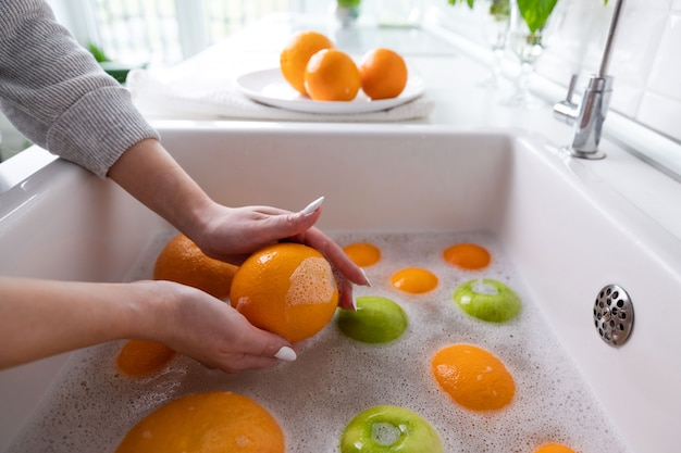 Woman washing apple, grapefruit, orange under faucet in the sink kitchen, soaking fruits in soapy water thoroughly washes after store.