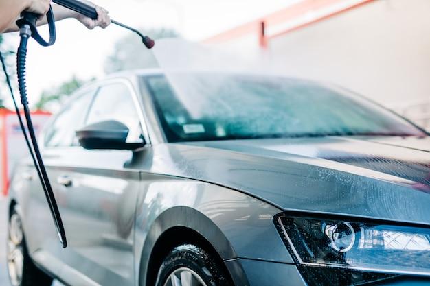 Woman washing car at car wash station using high pressure water machine.