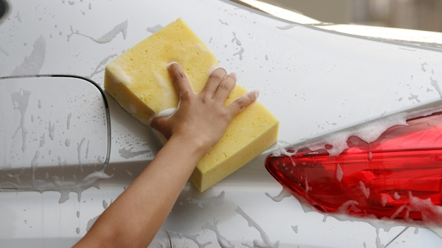 Woman washing a car with a sponge and soap