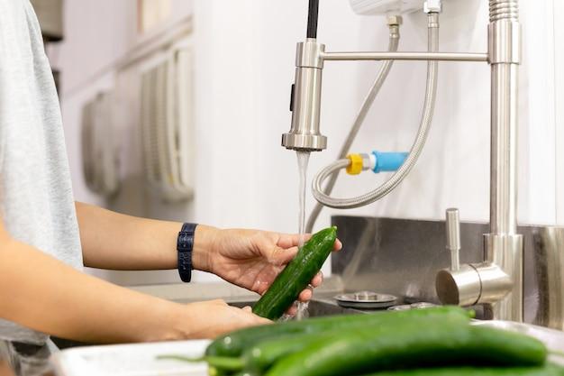 Woman washing cucumbers in running water in kitchen sink.