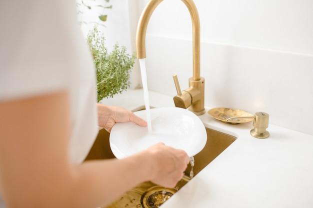 Женщина моет посуду на кухне. закройте руки женщины. домохозяйка чистит посуду