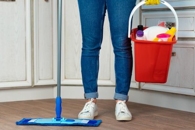 台所でモップで床を洗う女