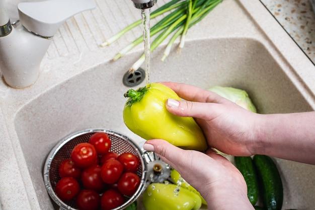 Woman washing fresh vegetables