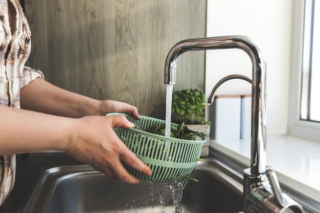 Женщина моет листья зеленого салата для салата на кухне в раковине.
