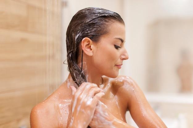シャワーの下で髪を洗う女性