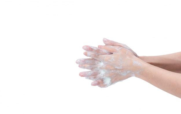 石鹸の泡と水で手を洗う女。