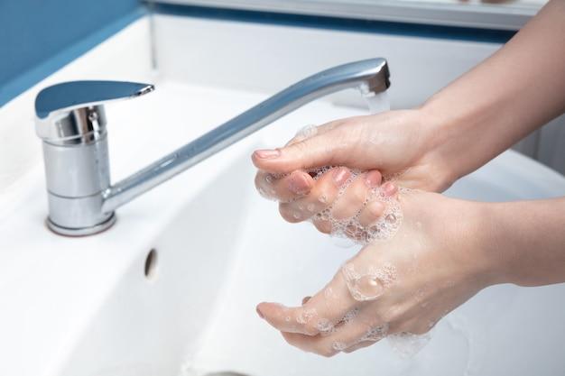 화장실에서 조심스럽게 손을 씻는 여자는 감염 예방을 닫습니다.