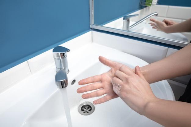 Женщина, тщательно мыть руки с мылом и дезинфицирующим средством, крупным планом. предупреждение распространения вируса пневмонии, защита от пандемии коронавируса. гигиена, санитария, чистота, дезинфекция. безопасность.