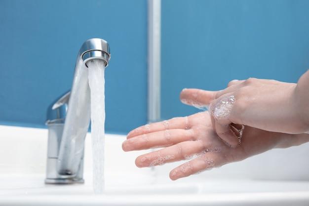 Donna che si lava accuratamente le mani con sapone e disinfettante, primo piano. prevenzione della diffusione del virus della polmonite, protezione contro la pandemia di coronavirus. igiene, sanitario, pulizia, disinfezione. sicurezza.