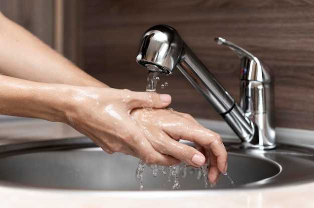 Woman washing hands in a sink