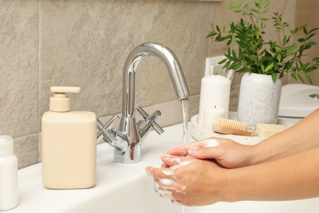 シンクの水道水の下で手を洗う女性
