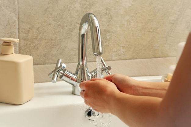 Woman washing hands under the water tap in sink