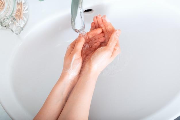 Женщина моет руки с антибактериальным мылом и водой. концепция гигиены. коронавирусная защита рук, гигиена, антисептик. дезинфицирующее средство для кожи для здравоохранения
