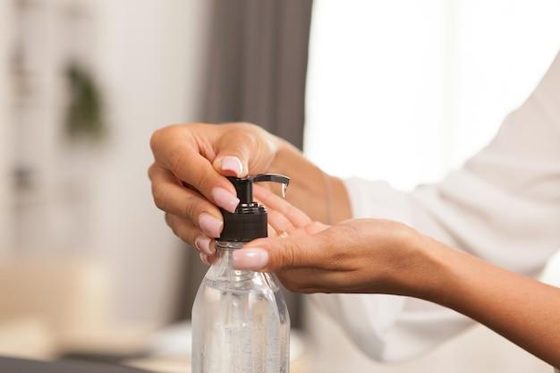 自宅で仕事をしながら消毒剤で手を洗う女性。