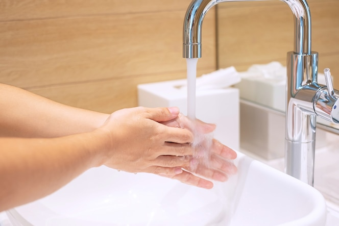 Woman washing hands with liquid soap