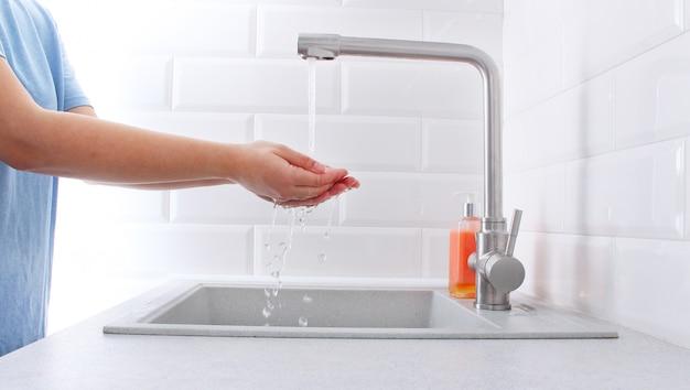 집에서 비누로 손을 씻는 여자.