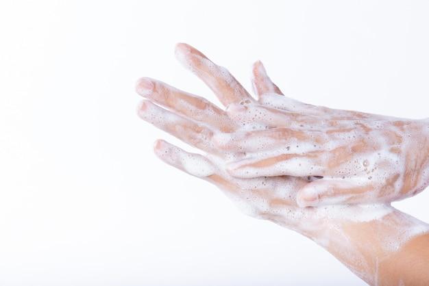 白い背景の上の石鹸で手を洗う女。ヘルスケアの概念。