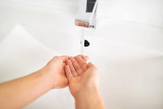 浴室の流しの上に石鹸で手を洗う女性