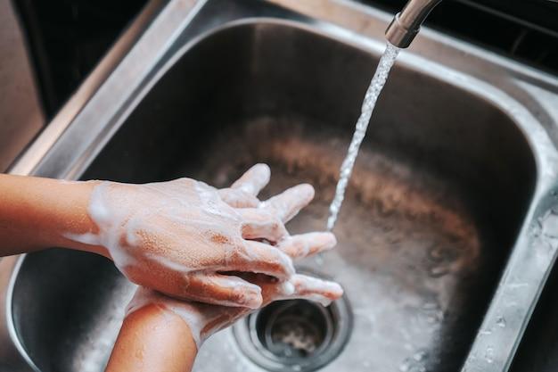 石鹸で手を洗う女