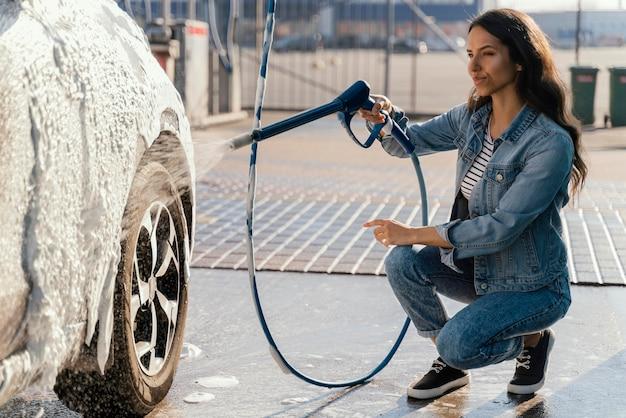 Женщина, моющая свою машину на открытом воздухе